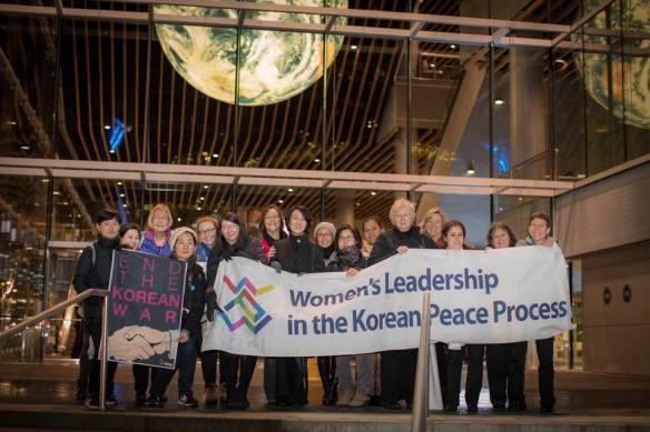 A group of about 20 Korean and Canadian women, with a banner saying Women's Leadership in the Korean Peace Process.